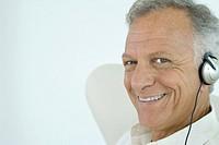 Mature man wearing headphones, smiling at camera