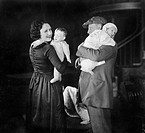 Father holding baby and mother holding a doll All persons depicted are not longer living and no estate exists Supplier warranties that there will be n...