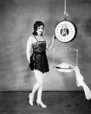Portrait of a young woman weighing her clothes on a weighing scale All persons depicted are not longer living and no estate exists Supplier warranties...