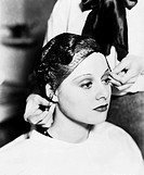 Hairdresser tying hair net on a young woman´s hair All persons depicted are not longer living and no estate exists Supplier warranties that there will...