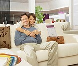Smiling couple on sofa in furniture shop