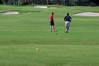 Two men playing golf in a golf course