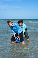 Mid adult couple playing rugby on the beach