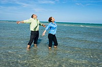 Mid adult couple standing on the beach with their arms outstretched