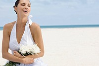 Close-up of a young woman holding a bunch of flowers on the beach