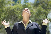 Businesswoman looking up with her arms raised