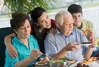Senior couple having lunch with their grandchildren