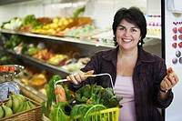 Portrait of a mature woman holding a shopping basket and smiling