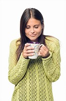 Close-up of a young woman standing and holding a cup of coffee