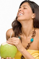Close-up of a young woman holding a peeled coconut and smiling