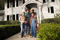 Portrait of a family in country clothes standing in front of a house