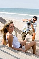 Man photographing a woman at the beach