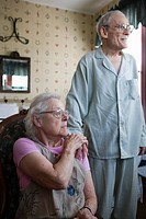 Seated senior woman affectionately patting senior man´s hand that is resting on her shoulder