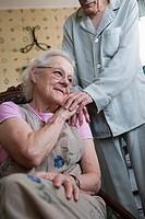 Senior woman sitting with senior man´s hand resting on her shoulder