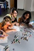 An art teacher teaching young students in art class