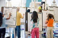 Boys and girls drawing on easels in art class