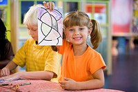 Girl 5_6 showing off her drawing with toothy smile