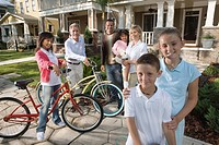 Family with young children standing with neighbors in front of house