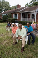 Portrait of interracial couple and family sitting in backyard