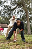Father and son playing football in backyard