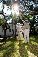 Rear view of mature couple standing under oak trees