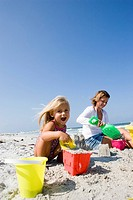 Mother and daughter building sandcastles on the beach