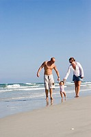 Young family strolling along the beach