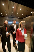 Portrait of business people riding in an elevator