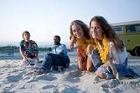 Hippies sitting on sand at beach at dusk