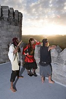 Pirates armed with a pistol and a sword looking over a castle parapet