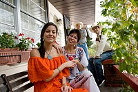 Portrait of a cheerful Tex_Mex family in front porch of house