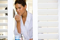 Young woman applying lipstick in mirror, portrait, view through shutters