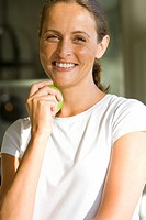 Woman with apple, smiling, portrait, close-up
