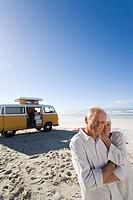Senior couple on beach by camper van, smiling, portrait