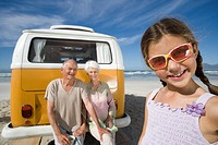 Girl 7-9 wearing sunglasses on beach by grandparents on back of camper van, smiling, close-up
