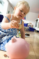 Girl 2-4 putting coin in piggy bank, low angle view