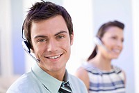 Man in headset by colleague, smiling, portrait, close-up