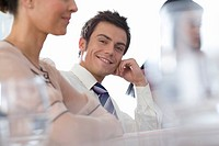 Businessman and women at table in meeting, portrait of man smiling differential focus