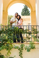 Young couple arm and arm by archway, low angle view
