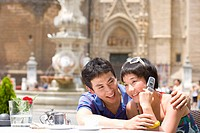 Couple at table outdoors, man embracing woman on mobile phone, smiling, close-up