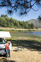 Couple by lake and motor home taking photograph of themselves with mobile phone, elevated view