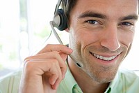 Young businessman wearing headset, smiling, portrait, close-up