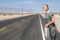 Businesswoman on side of road in desert with briefcase, side view