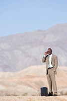 Businessman by briefcase using mobile phone in desert, smiling