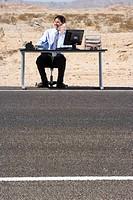 Businessman at desk on side of road in desert, using telephone