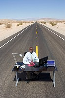 Businessman at desk in middle of road in desert, smiling, portrait, elevated view