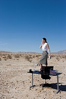 Businesswoman standing on desk in desert, side view