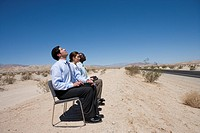 Businessman and woman with colleague in desert, on chairs in row, side view