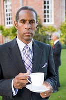 Businessman with teacup outdoors, portrait