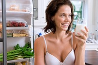 Young woman in underwear with drink by open door of fridge, smiling